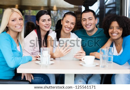 Smiling group of teenagers at cafe with tablet touch