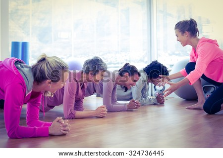 Smiling group of women exercising on floor in fitness studio - stock photo
