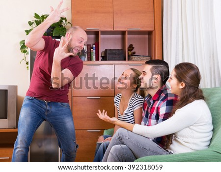 Smiling group of young adults having fun at house booze party - stock photo
