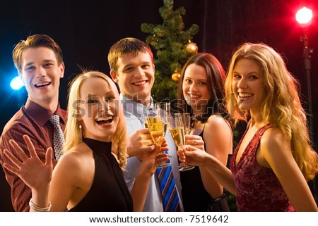 Smiling group of young people enjoying cocktails at christmas - stock photo
