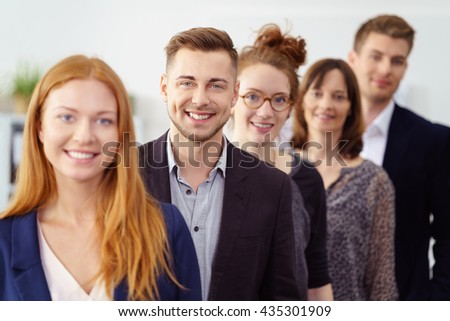 Smiling group of young professionals stand in line wearing business attire and lead by beautiful woman with red hair - stock photo