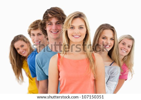 Smiling group standing behind one another at various angles while looking at the camera - stock photo