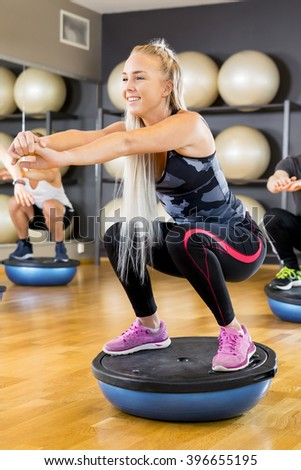 Smiling group training squats on half ball at fitness gym - stock photo