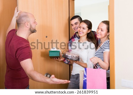 Smiling guests with cake and presents standing in doorway - stock photo