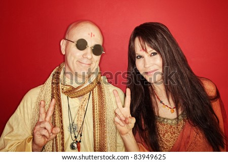 Smiling guru with woman gestures peace sign over maroon background - stock photo