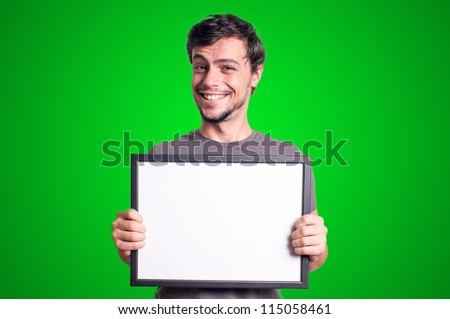 smiling guy holding empty board on green background