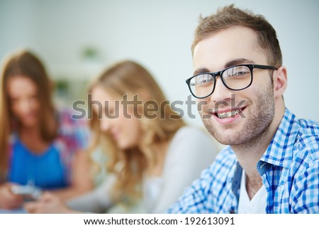 Smiling guy looking at camera with his groupmates on background - stock photo