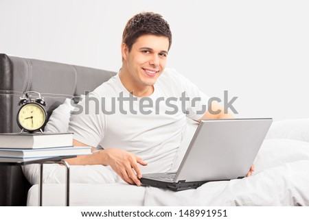 Smiling guy lying on a bed and working on a laptop computer - stock photo