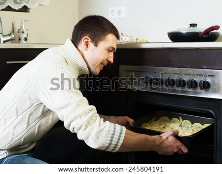 Smiling guy roasting meat in the oven at home kitchen