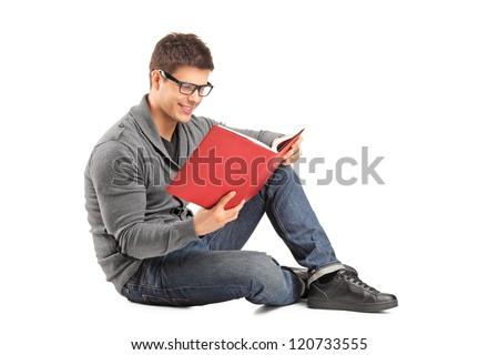Smiling guy sitting on a floor and reading a book isolated on white background - stock photo