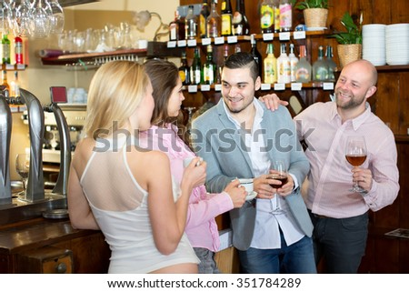 Smiling guys flirting with beautiful women in a bar