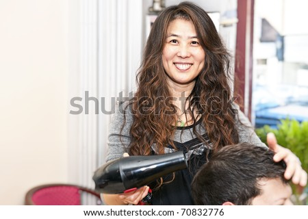 Smiling hairstylist drying hair with hairdryer in her salon - stock photo