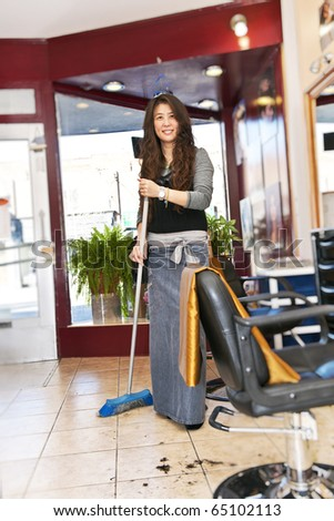 Smiling hairstylist sweeping hair clippings on floor in her salon - stock photo