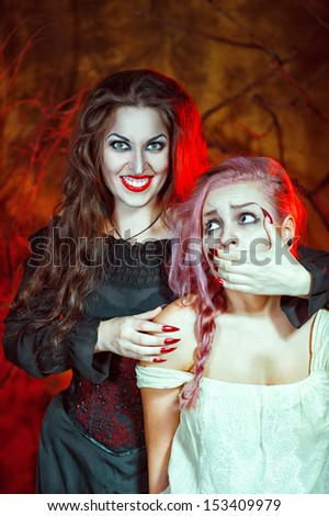 Smiling halloween witch and her victim - stock photo