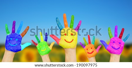 Smiling hands on summer background. Children's hands in colorful paint with smiles. Summer holidays and fun games concept. - stock photo