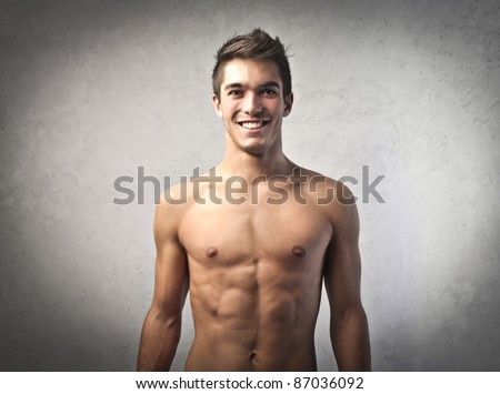 Smiling handsome bare-chested young man - stock photo