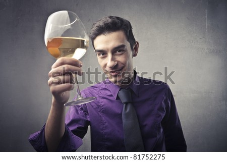 Smiling handsome businessman holding a glass of wine - stock photo