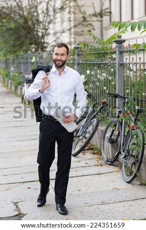 Smiling Handsome Businessman in Black and White Suit Walking on the Street with Coat on Shoulder While Holding Newspaper on Other Hand. - stock photo