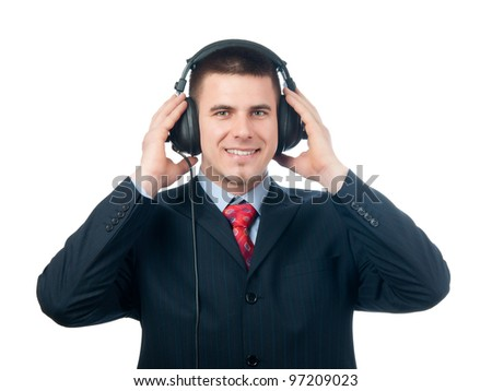 Smiling handsome businessman listening to music through the headphones isolated on white.