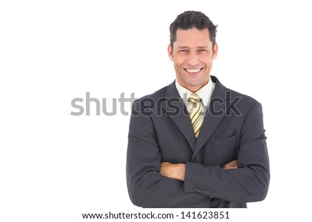 Smiling handsome businessman with crossed arms on white background - stock photo