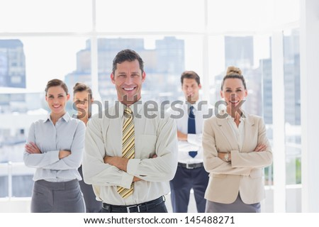 Smiling handsome businessman with his team in a modern office - stock photo