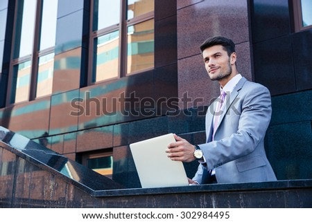 Smiling handsome businessman with laptop outdoors  - stock photo