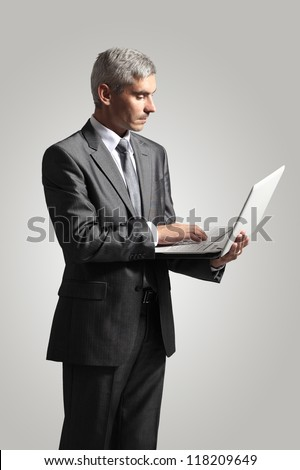 Smiling handsome businessman working with laptop. Isolated over white background