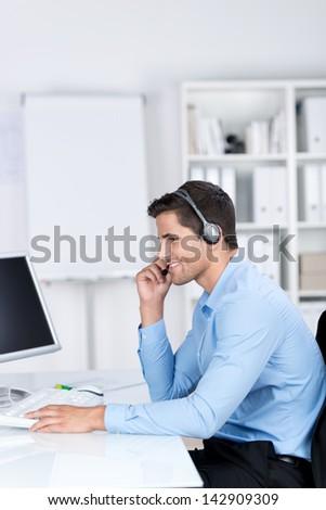 Smiling handsome caucasian businessman sitting at the desk in the office and using a headset and a desktop computer