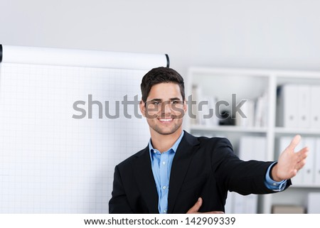 Smiling handsome caucasian businessman standing by the side of a blank flip-chart during a presentation in the office - stock photo