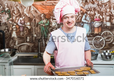 Smiling handsome confectioner, wearing in pink apron, hat and striped shirt, holding dripping pan with freshly baked gingerbread, in the kitchen with painted walls, waist up
