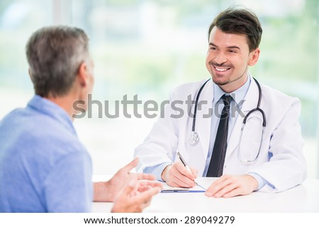 Smiling handsome doctor talking with patient at his office. - stock photo