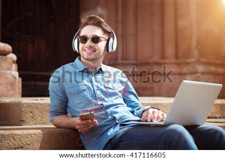 Smiling handsome guy listening to music  - stock photo