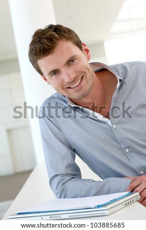 Smiling handsome guy standing in hallway - stock photo