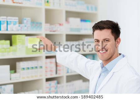Smiling handsome male pharmacist promoting a product holding it in his hand visible to the camera with a friendly smile - stock photo