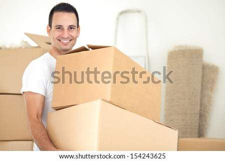 Smiling handsome man carrying packages during moving house - stock photo