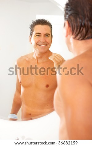 Smiling handsome man in the bathroom - stock photo