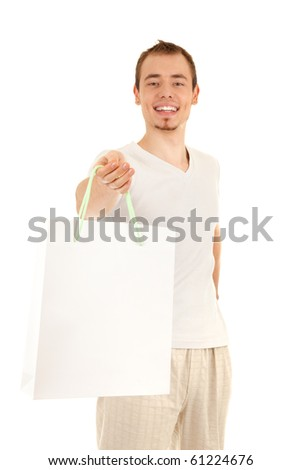 Smiling handsome man is presenting white gift paper bag, isolated on white background. Focus on man's eyes.