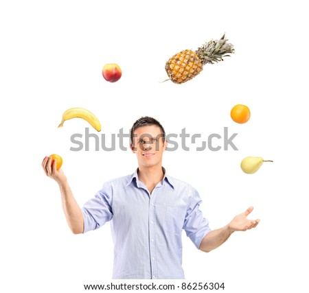 Smiling handsome man juggling fruits isolated on white background - stock photo