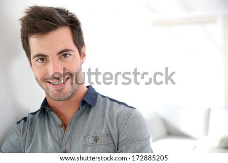 Smiling handsome man looking at camera - stock photo