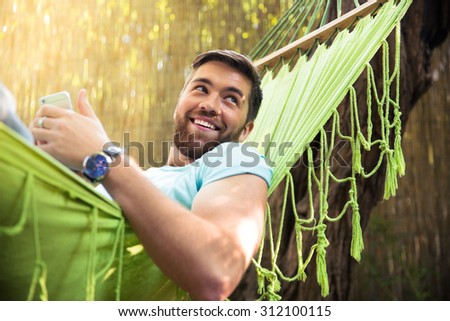 Smiling handsome man lying on hammok with smartphone outdoors  - stock photo