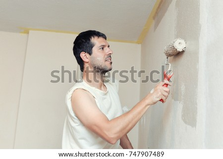 Smiling handsome man painting wall by roller at home. Repair, building and home concept