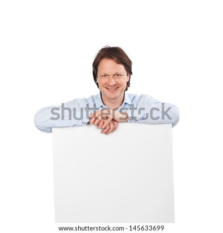 Smiling handsome man with a blank sign board leaning on the top in his shirtsleeves, copyspace for your text or advertisement - stock photo