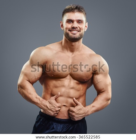 Smiling handsome man with muscular torso shows thumbs up sign - isolated on grey background. Sexy athlete showing ok - stock photo