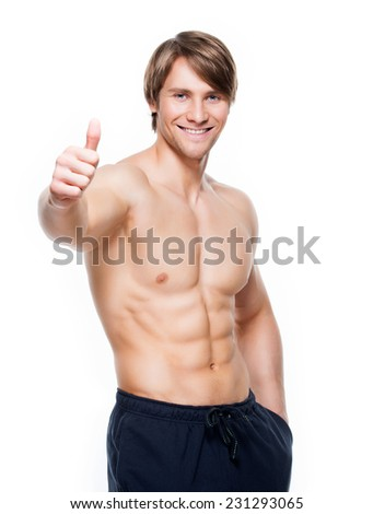 Smiling handsome man with muscular torso shows thumbs up sign - isolated on white background. - stock photo