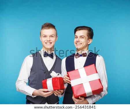 Smiling handsome men hipster style keep presents wrapped in red gift paper - stock photo