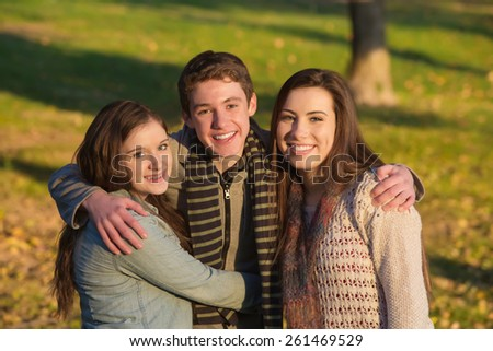 Smiling handsome teen male with happy girlfriends outdoors - stock photo