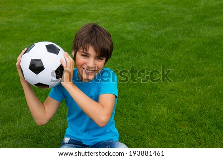 smiling handsome teenager boy holding football ball