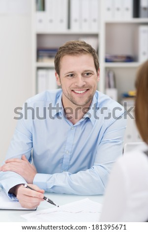 Smiling handsome young businessman having a discussion with a female co-worker as they sit at a desk analysing paperwork, view over her shoulder to his face