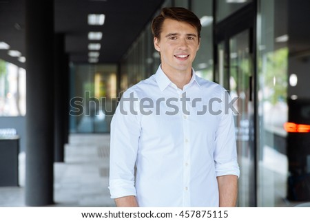 Smiling handsome young businessman standing near business center