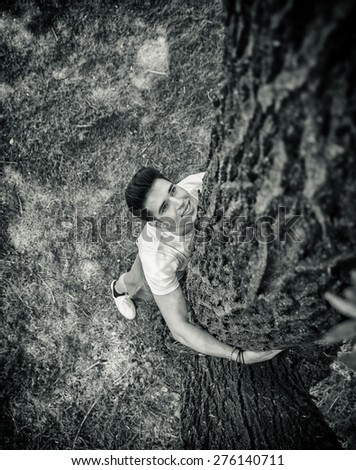 Smiling handsome young man hugging a tree, looking up, seen from up above. - stock photo